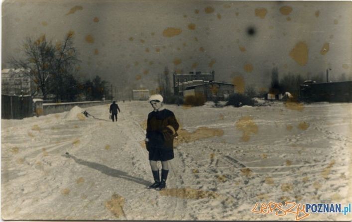 Zima 1968 albo 1969 roku. Pani Halina na spacerze. Właśnie przystanęła na środku Dolnej Wildy. To cicha i spokojna ulica. Nie widać żadnego samochodu, nawet na śniegu niewiele śladów mechanicznych pojazdów. Po lewej, w oddali kamienice przy ulicy Krzyżowej, po prawej budynek